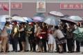 Tourists holding umbrellas visit Tiananmen Square in Beijing. Photo: Reuters