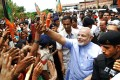 Narendra Modi (in blue) greets supporters upon arrival in Goa on Friday. Photo: AFP