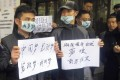 Demonstrators hold banners outside the headquarters of Southern Weekly newspaper in Guangzhou, January 8, 2013. Photo: Reuters