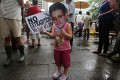 A child holds a cut-out of Edward Snowden at the rally. Photo: Sam Tsang