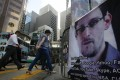 People walk past a banner supporting Edward Snowden at Central, Hong Kong's business district. Photo: AP