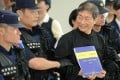 """Chang An-lo displays a document that reads """"On China Two System"""" as he is escorted away by police after landing at the Songshan Airport. Photo: AFP"""