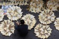 A worker in Western District dries shark fins outside a store. Photo: SCMP