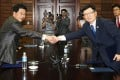 Suh Ho (right), head of the South Korean working-level delegation, shakes hands with his North Korean counterpart Park Chol-Su after their talks. Photo: AFP