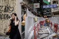 A woman blocks her ears as she walks past roadworks in Hong Kong. Photo: AFP