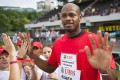 Asafa Powell trains with children in a special session in Geneva, Switzerland, on July 2. Powell has tested positive for banned stimulants. Photo: EPA