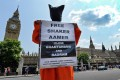 Campaigners wearing Guantanamo Bay detainee jump suits protest outside the parliament in London. Photo: EPA