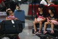Children stranded at the Beijing Capital International Airport after their flights were cancelled due to heavy rain. Beijing and Shanghai rank at the bottom of 35 major international airports for flight delays and cancellations in a recent survey. Photo: AP