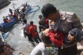 A police officer carries an unconscious child from the boat that capsized after hitting a reef off the coast of Sukapura, in Cianjur. Photo: Reuters