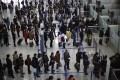 Passengers queue up for a security check at Pudong International Airport in Shanghai. Photo: AP