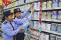 Chinese commercial law enforcement personnel inspect milk powder products at a supermarket in Lianyungang, Jiangsu province on Tuesday. Photo: Reuters