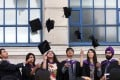 Students from the London School of Economics & Political Science (LSE) throw their mortar boards into the air in celebration during a ceremony for university graduates. Photo: Bloomberg