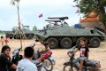Cambodian children sitting on motorbikes near armored personnel carriers on the outskirts of Phnom Penh. Photo: AFP