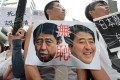 Demonstrators display a placard with images of Japan's Prime Minister Shinzo Abe at a rally in Taipei yesterday. Photo: AFP