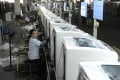 Workers assemble washing machines Hefei Rongshida Sanyo Electric production line in China. Photo: Reuters