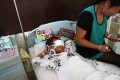 A boy lies on his hospital bed with his eyes covered with bandages as his mother sits next to him in Taiyuan, north China's Shanxi province on Tuesday. Photo: AFP