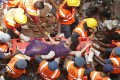 Rescue workers use a stretcher to carry a victim across the rubble after the collapse of two residential buildings in Vadodara city. Photo: Reuters