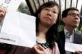 Alpais Lam with lawyer Andrew Cheng shows the threatening letter before entering Tai Po police station to report it. Photo: K. Y. Cheng