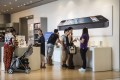 Customers look at devices on offer beneath a poster of an iPhone 5 smartphone at an Apple retailer in Beijing. Photo: EPA
