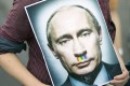 Protesters at a demonstration in Berlin show off a poster of Vladimir Putin with a rainbow-hued moustache. Photo: EPA