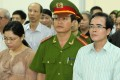 Lawyer Le Quoc Quan (right) and accountant Pham Thi Phuong stand with a policeman during their trail at a court in Hanoi. Photo: Reuters