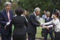 Kerry (left) and Hagel receive flowers at the cemetery. Photo: Reuters