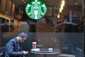 A man takes a rest at a Starbucks outlet in Shanghai. Photo: Xinhua