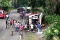 Filipino villagers view a wrecked passenger bus and a truck on a side of a road following an accident in the town of Atimonan, Quezon province, Philippines. Photo: EPA