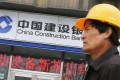 A worker walks past a branch of China Construction Bank (CCB) in Beijing. Photo: Reuters