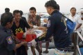 Thai rescuers carry an injured tourist on to the pier after being rescued from the sea after the boat accident in Pattaya. Photo: AP