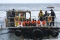 Australian customs officials and navy personnel escort rescued asylum-seekers onto Christmas Island. Photo: Reuters