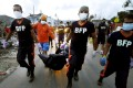 Firemen carrying the body of a victim in Tacloban. Photo: AP