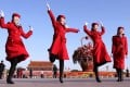Female hotel attendants in red uniforms jump on Tiananmen Square in Beijing during the Communist Party's 18th Congress in November 2013. Photo: SCMP/Simon Song