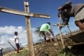 Survivors bury an uncollected body on the side of a road in the devastated town of Palo, Leyte province. Photo: EPA