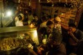 People at a food stall eat under the glow of candles and a TV camera's lights during the electricity blackout in Caracas. Photo: EPA