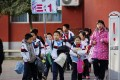 A student holds a placard showing the name of his class as he leaves school with his classmates at a Chinese elementary school. Photo: Reuters