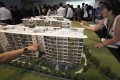 Prospective buyers look at a model of a condo development. Photo: Reuters