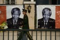 A paramilitary policeman walks past portraits of the late Nelson Mandela outside the South African embassy in Beijing. Photo: AFP