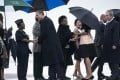 Barack Obama, his wife Michelle (under umbrella) and former US president George W. Bush arriving in South Africa. Photo: AFP