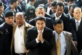Abhisit Vejjajiva (centre) arrives at court yesterday. Photo: AFP