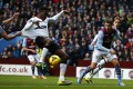 Danny Welbeck scores the first of his two goals against Aston Villa despite having his shirt pulled by an opponent. Photo: Reuters