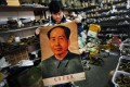 A clerk shows a wall hanging bearing the image of China's late Chairman Mao Zedong at an antique shop in Beijing. Photo: Reuters