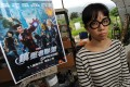 Political activist Ger Choi Tze-kwan stands next to a parody poster of movie The Avengers in May last year.