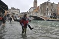 People walk in high water near the Ponte delle Guglie in Venice, Italy, as high tides flood the city. Photo: AP