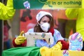 A Greenpeace activist in Budapest, Hungary, carries out a performance in a street protest on Tuesday in which she pretend to be sewing contaminated clothes with chemicals represented by little monsters. Photo: AFP