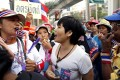 A Thai voter (centre) argues with anti-government protesters blowing whistles as they block a polling station during advance voting in Bangkok. Photo: EPA