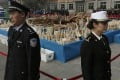 Customs officers stand guard in front of confiscated ivory in Dongguan, southern Guangdong province, China Monday, Jan. 6, 2014. Photo: AP