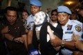 Schapelle Corby, covered by a veil, is escorted by police after being released from prison on Monday. Photo: Reuters