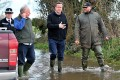 British Prime Minister David Cameron (centre) talks to Bridgwater and West Somerset MP Ian Liddell-Grainger (left) and farmer Tony Davy (right) during a visit to flooded areas. Photo: EPA