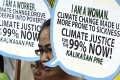 Protesters display placards at a rally in Manila to mark World Climate Day. Photo: AP